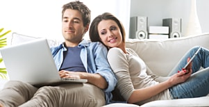 Man and woman on sofa reading ebooks on laptop and tablet.
