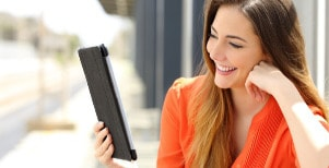 Happy woman reading good book on a tablet.