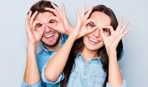 Couple using hands to accentuate their eyes