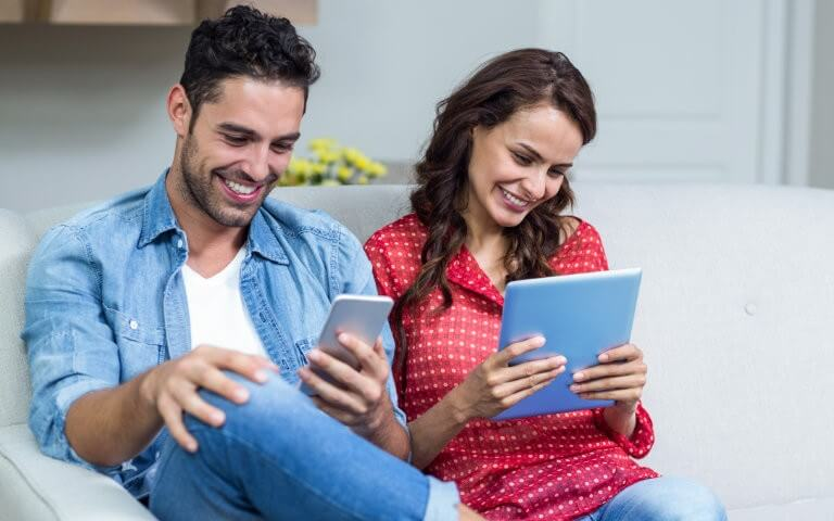 Happy couple using smartphone and tablet to read ebooks
