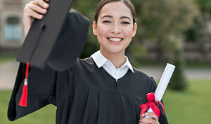 Happy student on graduation day holding diploma.