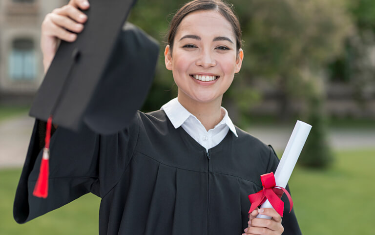 Smiling girl student on graduation day holding diploma.