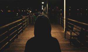 Hooded person walks on boardwalk at night.