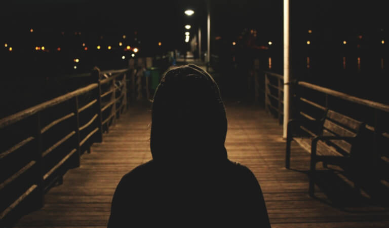 mysterious hooded figure on boardwalk at night