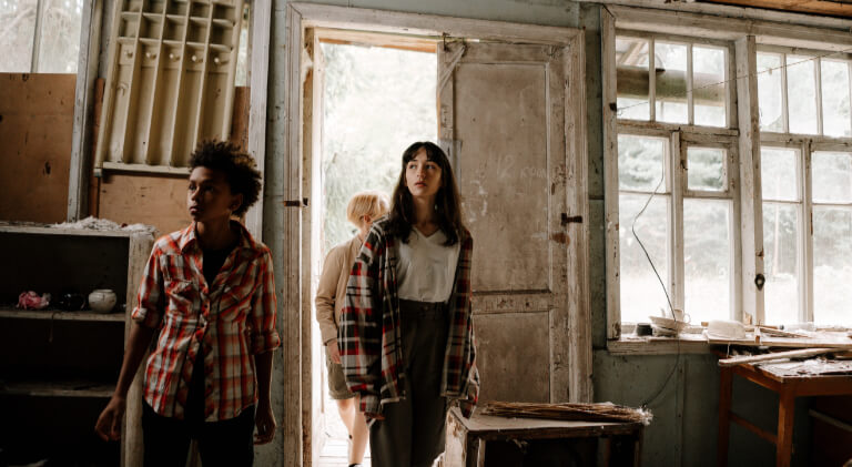 Three teens enter a creepy old cabin in the woods